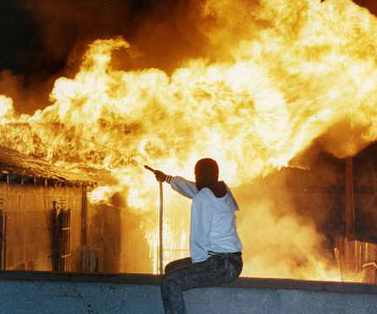 A resident vainly attempts to fight a raging fire at 79th Street and Normandie Avenue using a garden hose. (April 29, 1992)  Source: Mike Meadows / Los Angeles Times