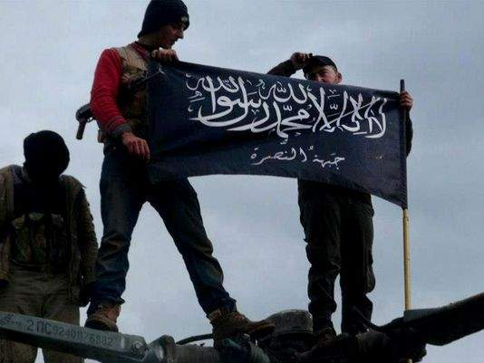 Jan. 11, 2013, file citizen journalism image provided by Edlib News Network, ENN, which has been authenticated based on its contents and other AP reporting, shows rebels from al-Qaida affiliated Jabhat al-Nusra waving their brigade flag on the top of a Syrian air force helicopter, at Taftanaz air base that was captured by the rebels, in Idlib province, northern Syria. / Edlib News Network ENN / Associated Press (Source: Detroit Free Press/ USA Today).
