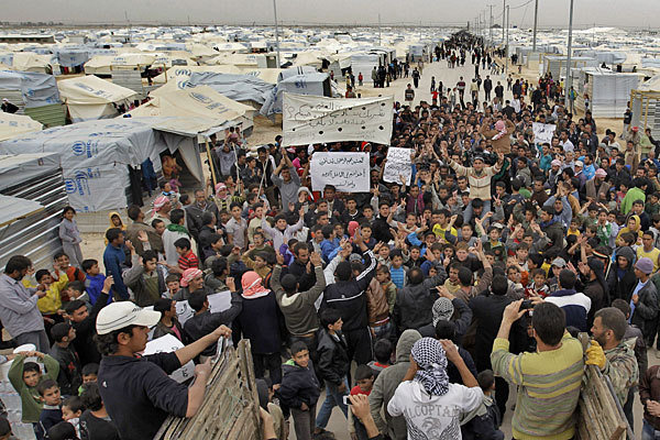 """Syrian refugees take part in a demonstration this year at the Zaatari camp in Jordan, near the border with Syria"" reports Los Angeles Times in California (Image Credit: Khalil Mazraawi / AFP/Getty Images)."