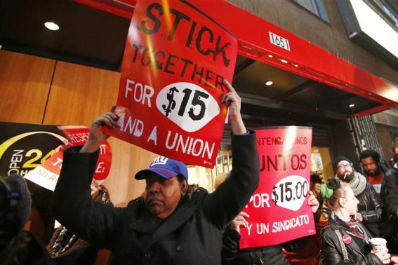 Fast food workers attend a protest against McDonald's outside one of its restaurants in New York, December 5, 2013. Notice the signs in New York are in English and Spanish. Photo credit: REUTERS/Eduardo Munoz