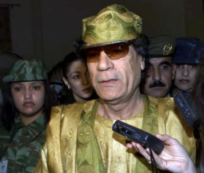 "Libya's Former (Killed in Action) Col. Qaddafi seen here with his all-female only (""Virgin"") bodyguards.  Qaddafi never trusted a male to protect him. He feared that they would try to overthrow him. His military commanders tended to be male however. (Image Credit uncited. Please advise for credit)."