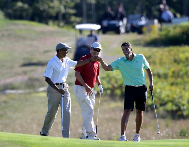 CORRECTS DATE - President Barack Obama, left, bumps fists with Cyrus Walker, right, cousin of White House senior adviser Valerie Jarrett, as Glenn Hutchins, center, looks on while golfing at Vineyard Golf Club, in Edgartown, Mass., on the island of Martha's Vineyard, Wednesday, Aug. 20, 2014. Obama is taking a two-week summer vacation on the island. Golf caddie at right is unidentified. (AP Photo/Steven Senne)