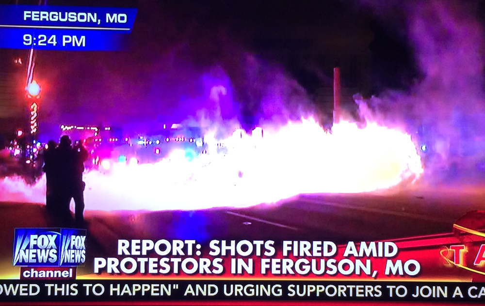 """Protestors"" (Rioters) launch firebombs at police creating a brief wall of fire. Shots also fired in the direction on police, reports claimed. Police responded by firing teargas to disburse the unruly crowds. Image Credit: Fox News. Nov. 24, 2014."