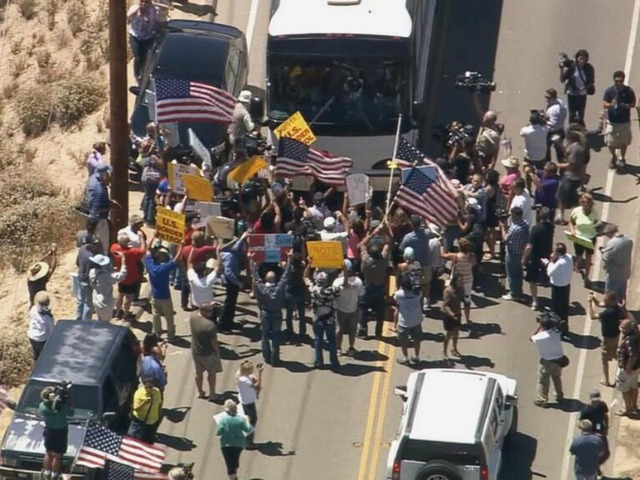 Protestors block DHS/ INS buses in July 2014 where the government agencies were facilitating what the drug cartels and other human traffickers could not successfully do: Finishing transporting illegal aliens throughout the USA (Image Credit CBS).