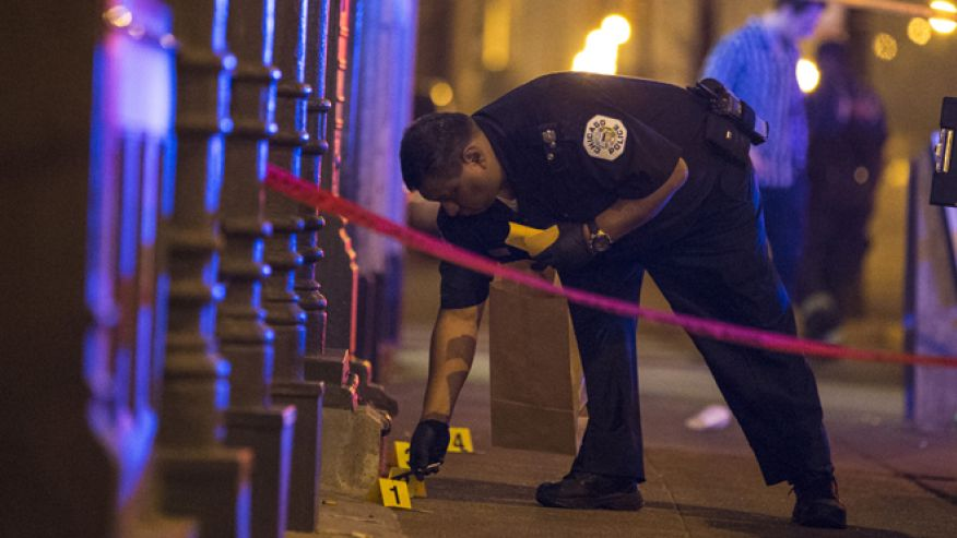 A Chicago police officer collects evidence at a crime scene where a man was shot in the city. (Reuters, July 5, 2015. Source: Washington News Daily.)