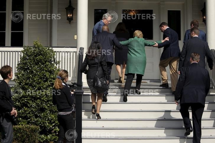 Hillary Clinton appears unable to walk up a few steps on her own, requiring assistance from two apparent Secret Service agents. Image Credit: Reuters.