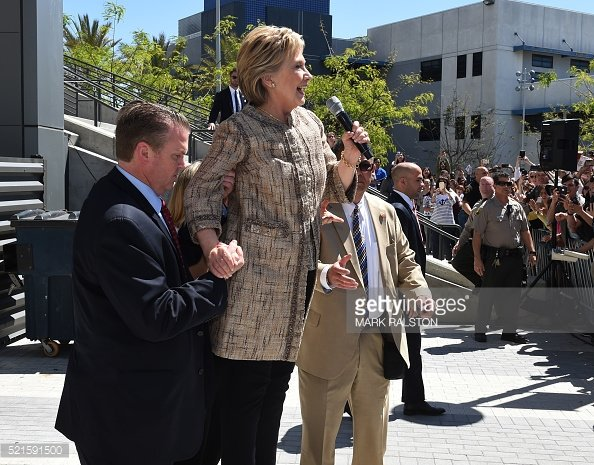 Hillary Clinton appears unable to stand on her own, requiring assistance from apparent Secret Service agent. Image Credit: Mark Ralston/ Getty Images.