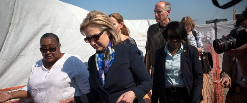 Secretary Hillary Clinton, her advisor/ lawyer, Cheryl Mills (right in light blue), and others arrive in Haiti. Clinton was in charge of distributing U.S. aid to the country (Image Credit: ABC News).